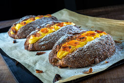 Sweet bread with a pudding and apricot filling on a baking tray