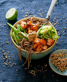 Soba noodle bowl with fried salmon, green asparagus and a sesame seed and lime dip