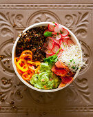 A bowl with lentils, guacamole, radishes, peppers and beansprouts