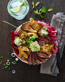 A bowl with beef steak, oyster mushrooms, freekeh, herb cream and radiccio