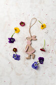 A wooden Easter bunny with tufted pansies and daisies