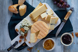 A French cheese platter with nuts, jams and grapes