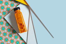 Mango and pumpkin smoothie bottle over retro style geometric textures