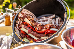 A pot being lined with bacon and layered with meat, onions and peppers