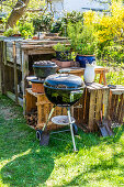 A charcoal barbecue and a Dutch oven in a garden