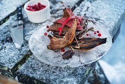 A winter barbecue: grilled quail served on an ice plate (Norway)