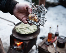 A winter barbecue: a hand holding a baked potato
