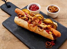Hot Dog mit Röstzwiebeln, Essiggurken, Senf, Mayo und Ketchup
