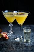 Passion fruit Martini also known as Pornstar Martini in two cocktail glasses decorated with slice of passion fruit with a chaser of Champagne