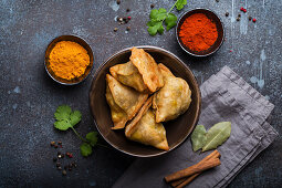 Indian samosas - fried pastry with savoury filling, served in bowl with spices and fresh cilantro