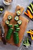 Springlike vegan maki sushi with spinach, avocado, carrots, mango and shallots on wooden board