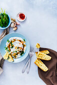 Turkish eggs with a butter sauce accompanied by spinach, red pepper flakes and toasted bread