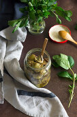 Jar of yummy marinated artichokes with basil leaves placed on brown table near napkin