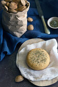Fresh almond bun with dried herbs placed on napkin on gray tabletop