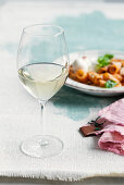 A glass of white wine in front of a plate of pasta