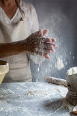 A woman sprinkling flour on a marble surface