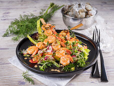 Fried shrimp kebab on a colourful salad