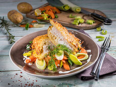 Cod fillets coated in potato, with leek, carrots and dill