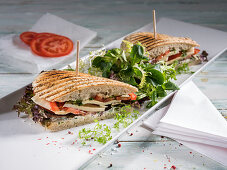 A grilled panini with tomato, mozzarella, lettuce and chervil