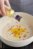 Olive oil being added to chopped garlic and chilli peppers
