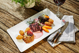 Pollak sauerbraten with red wine sauce, vegetables and croquettes