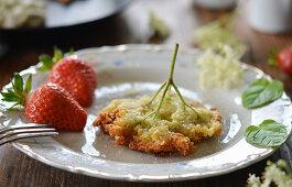 Elderflowers in pancake batter with fresh strawberries and sugar