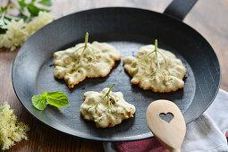 Elderflowers in pancake batter in a pan