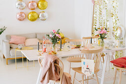 Table set for party in festively decorated living room in pastel shades