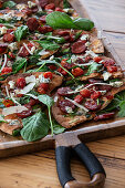 Chickpea flatbread with chorizo, spinach, cherry tomatoes and blue cheese