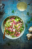 Colourful couscous salad with beetroots, fresh spinach and feta cheese. Salad is sprinkled with hazelnuts and dill