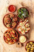 Various tapas - patatas bravas, croquetas with serrano ham, fried padron peppers, shrimps with garlic (Spain)