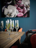 Champagne with rosemary in champagne glasses on a table in front of a blue wall