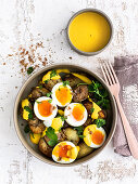 Soft-boiled eggs on coriander potatoes with a spicy pepper sauce