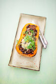 Butternut squash filled with minced meat and black beans on a tray