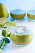 Glasses of green smoothies with pear, banana and spinach