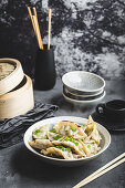 Asian dumplings in bowl, chopsticks, bamboo steamer, plates
