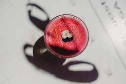 From above bubble frothy tasty fragrant pink smoothie with flowers in glass on wooden table