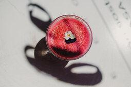 Pinkfarbener Smoothie mit Blüte von oben
