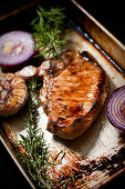 Fried pork chop with red onions, garlic and rosemary