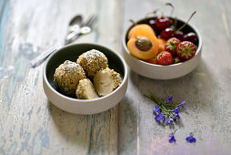 Vegan potato dumplings with pumpkin seed crumbs, and a bowl of fruit