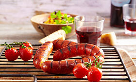 Grilled chorizos with salad, cherry tomatoes and baguette (Argentina)
