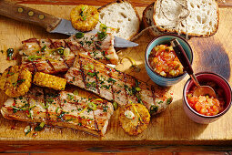 Grilled pork belly slices with a tomato and courgette chutney, corn cobs and white bread