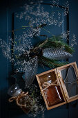 Two jars of honey, gypsophila and glass pine cones on blue surface