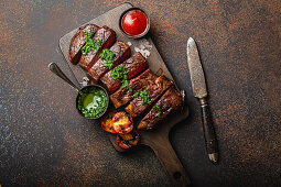 Grilled or fried and sliced marbled meat steak with fork, tomatoes as a side dish and different sauces on wooden cutting board, top view, close-up, stone rustic background