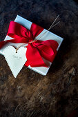 Gift wrapped with red bow and 'Thank you' written on heart-shaped tag