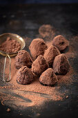Truffle pralines dusted with cocoa powder on a dark surface