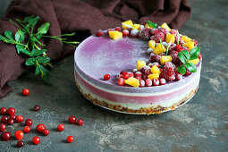 Vegan raw cake with lemon, cranberry, raspberry and blueberry, banan, cashew cream, coconut butter and coconut milk