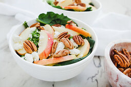 Served bowls with cut apple and pecan salad on table with apple and walnuts