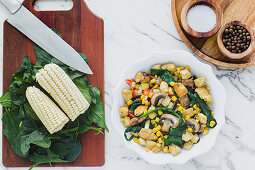 Served bowl with mushrooms corn and cut chicken on table with corn leaves of greenery on cutting board and condiments
