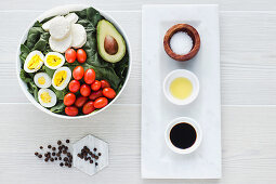 Served bowl of salad with spinach eggs avocados tomatoes and mozzarella cheese on table with condiments sauces